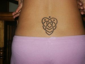 "Left upper back (shoulder blade) Celtic motherhood tattoo. ""The Celtic motherhood symbol looks like 2 hearts made out of knot work. One heart is lower than the first heart and both hearts are intertwined in a continuous knot. To add children to the Celtic motherhood symbol, you add dots. 1 dot per child. These dots can be placed anywhere inside or outside the motherhood symbol."