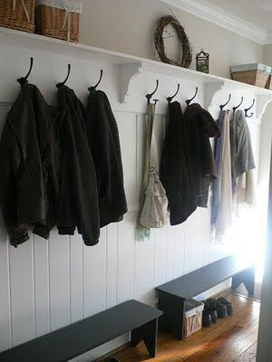 Paneled wall with shelf and hooks in mudroom