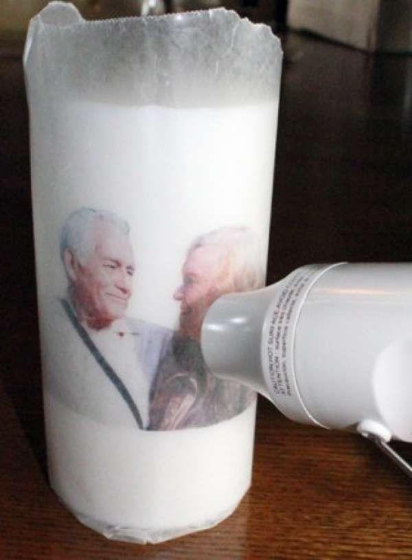 Imprimez la photo de votre choix sur du papier de soie et transférez-la sur une grande bougie blanche grâce à l'air chaud du sèche-cheveux.
