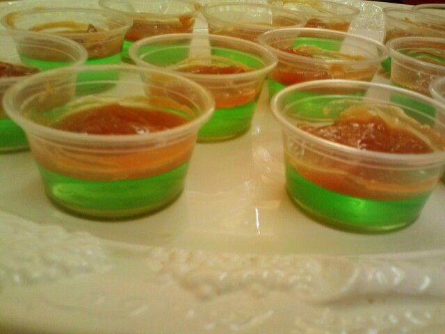 Caramel apple jello shots! Yum! Vodka, sour green apple jolly rancher jello, caramel dip  Recipe:  -1 6oz pkg sour apple joll rancher jello -Stir in 2 cups boiling water -Stir in 1 cup cold water -Stir in 1 cup liquor (vodka) -pour in plastic shot cups  -Chill 3 or more hours in fridge -evenly spread ready made caramel dip over each jello cup once firm -Ready to serve!