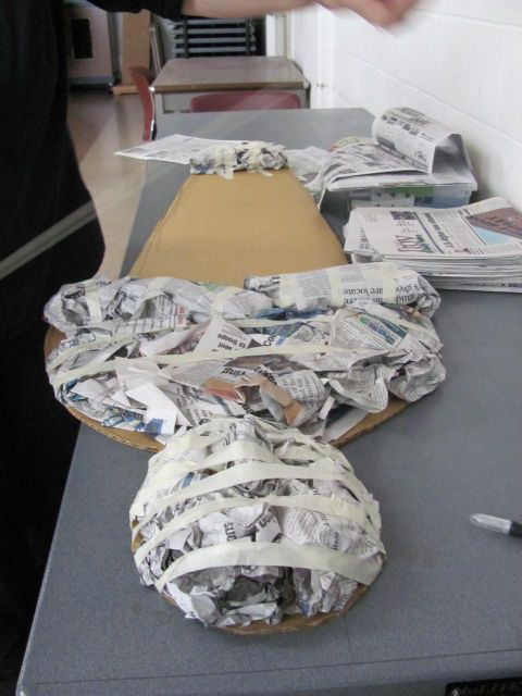 Making a mummy: cutting the cardboard to shape, smooshing newspaper and taping it in place