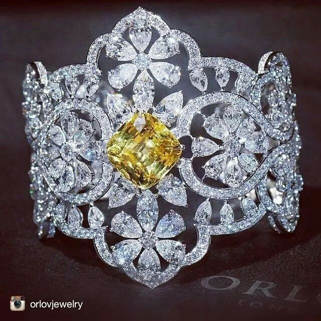 Yellow diamond centering white diamonds ring.