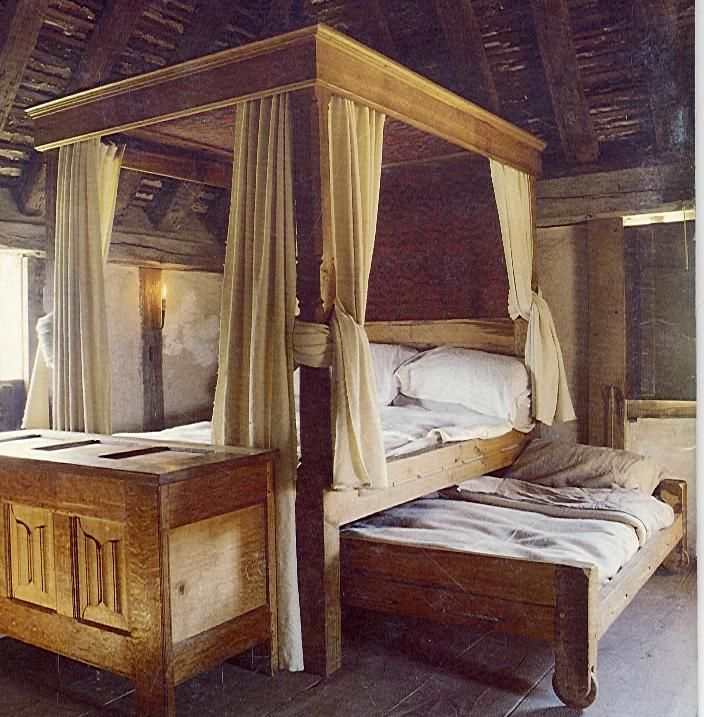 A reproduction of 16th century English poster bed and trundle bed.  Canopy beds with opulent draperies were stylish and functional (kept the cold out) in medieval castles.
