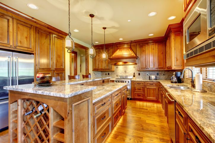 Huge natural wood kitchen with wood cabinets, wood flooring and wine rack on the end of the island. Counter tops are granite