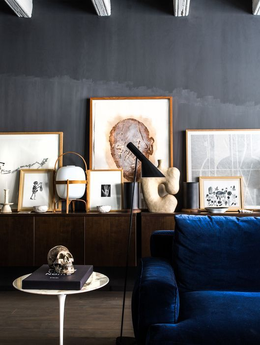 Dark blue velvet couch in an living room with dark gray walls. We love the gallery with wooden picture frames.