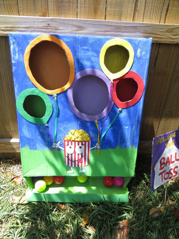 "Carnival birthday party: made ball toss game by cutting holes in a thin tall box. Added paint and a cute character to hold the ""balloons"". I used a few of my kids ball pit balls to toss. Easy, cheap. #carnivalgame #balltoss"