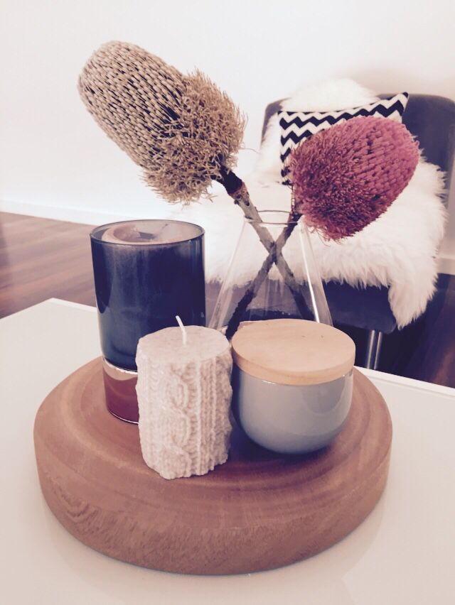 Coffee table display. Timber board, banksia, copper candle holder, knitted look candle.