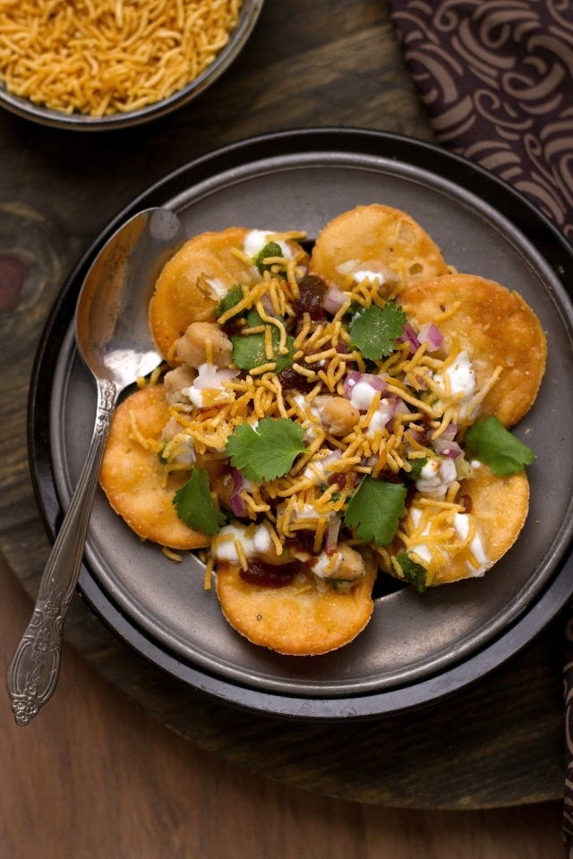 "Papri or Papdi are deep fried,wafer like salted discs which are served with a ""to taste""  assortment of boiled chickpeas & potatoes. hari (green) & imli (tamarind) chutneys,chopped /grated vegetables, powdered spices & yogurt. Its messy, crumbly, tangy, crunchy..oh so good!"
