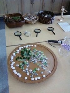 """Display rocks, gems & found materials onto a lazy susan. This activity can be tied into maths for sorting, graphing, counting, 1 to 1. Or an abstract art glueless mosaic activity can come from this. To the centre you can again add paper to allow the children to draw their creations & display them"" ("",)"