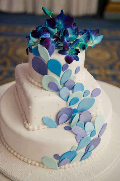 Modern three tier white cake with pearl beads, purple, blue and teal fondant accents and blue gradient snap dragon flowers.