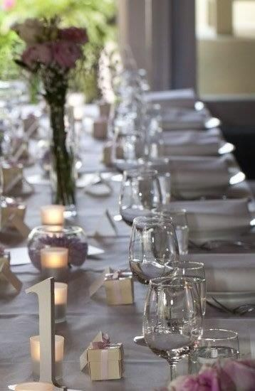 Simple elegance created by low candles, dahlias, roses and baby's breath spray,  pearlescent table numbers and bonbonniere