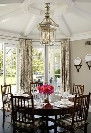 Elegant dining room with tan walls, tolie print curtains, floor to ceiling French doors and paned windows, Queen Anne dining chairs with striped set cushions and a brass lantern style pendant light