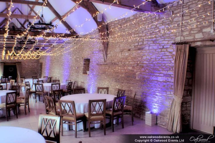 Purple uplighting and a fairy light canopy in the barn at Caswell House. Wedding lighting by Oakwood Events