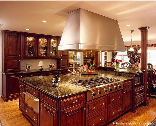 Dark Cherry cabinets, stainless steel appliances, hardwood floors, and granite counter tops. Yes.