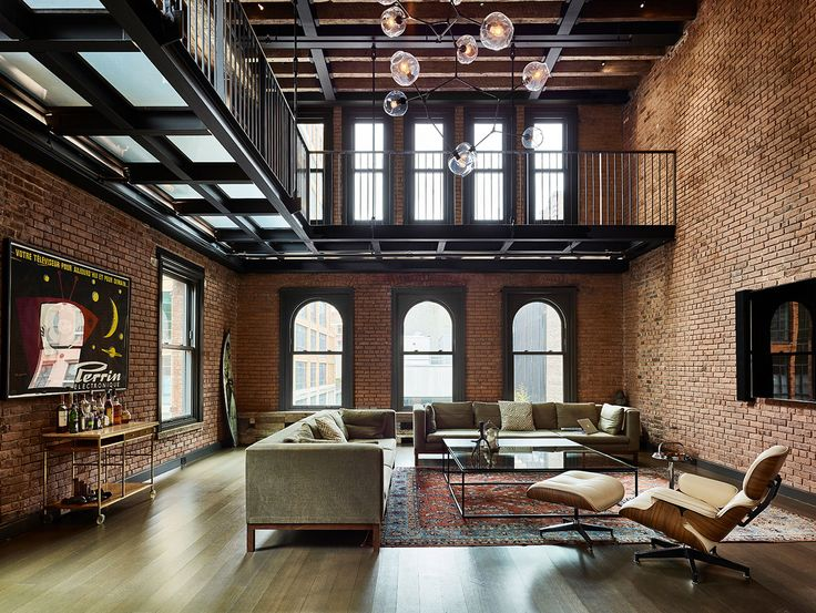 room living area with lots of exposed brick sits beneath a metal catwalk in this loft in new york city