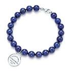 Tiffany & Co. | Item | Return to Tiffany™ small round tag in silver on a lapis lazuli bead bracelet.