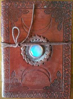 This Triple Moon blank leather journal is garnished with moonstone inside its center full moon, encircled by leather it's woven stitching, with the embossed crescent moons on top and bottom, it's bord