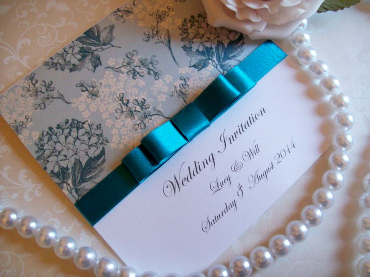 Teal wedding invitations with a pearl effect paper featuring hydrangeas and blossom and a very pretty teal bow