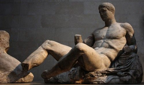 Figure D (commonly identified as Dionysos) from the East Pediment of the Parthenon. We can see his legs, and where his feet would have been attached. He reclines on a rock, which is covered by a mantle and an animal fur. Figure D is the only pediment sculpture with an intact head. He glances to the left, towards the rising sun of Helios, one of whose four horses can be seen (only two are at the British Museum, the other two are in Athens). (Photo by James Lloyd at the British Museum) -- AHE