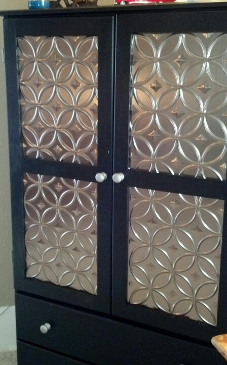 """Unfinished pine armoire painted with enamel paint.  I used plastic """"tin"""" panels for the door panels."""