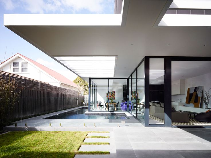 Kew Renovation by Canny Design. White cantilevering roof over alfresco area, dark frames, modern pool