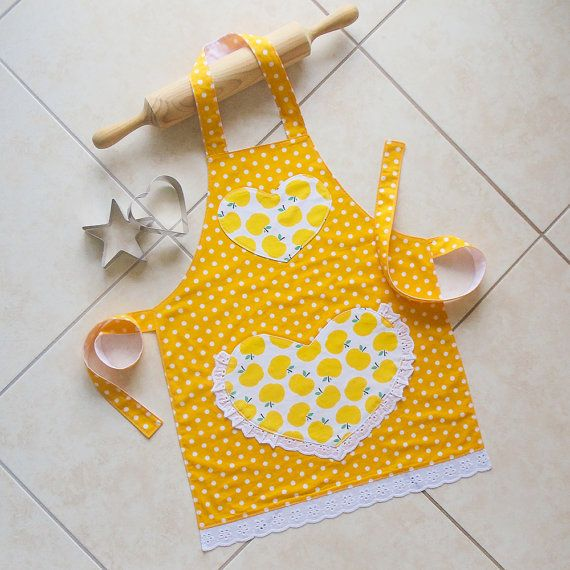 """Kids yellow kitchen craft art play apron. Lined girls cotton apron with pretty heart pocket and cute yellow apples and polka dots print.  """"Sugar and"""