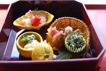 そもそも懐石料理とは精進料理から発展した。禅宗である臨済宗の妙心寺は東林院を始め精進料理を振る舞う塔頭(たっちゅう)が多い。食することと同等に、店の主人と客との「一期一会」を重んじる。   懐石料理の「オードブル」を「八寸」と呼ぶ。様々な料理が飾られ鮮やかだが、八寸皿に盛られたのが名前の由来だ。最初に主人と客が閑談するのがこの「八寸」の時で、緊張をほぐし、リラックスの時間を演出する。懐石料理には先付、吸物、煮物、焼物など様々な献立があるが、これから始まるコース料理との出会い、主人との邂逅を印象づける。   3皿に小分けされた料理は、「ほうれん草のお浸し」「ぬかご、栗、サツマイモ揚げ」「長いも昆布、にんじんの焚き物、千枚漬け」だ。「ぬかご」(=むかご)は山芋の葉にできる小芽で、油でさっと揚げるとスナック感覚で食べられる。塩を付けて食べると、イモのような食感が楽しい。最初から玉乃光の酒が進む。