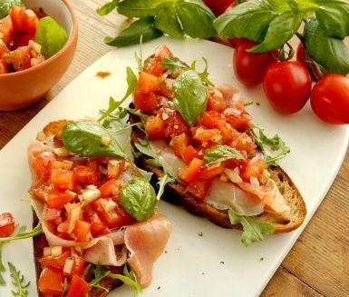 En tjusig förrätt med italienska förtecken, eller en charmig liten rätt på smörgåsbordet. Till bruschetta ska det vara lufttorkad skinka och en röra på solmogna tomater, vitlök, olivolja och balsamvinäger. Och italienskt bröd såklart!