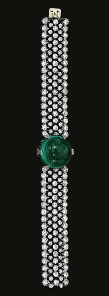 FINE  EMERALD  AND  DIAMOND  BRACELET,  CIRCA  1915	  	  Centring  on  a  circular  cabochon  emerald  highlighted  with  circular-  and  single-cut  diamond  set  motifs,  to  an  articulated  wide  band  designed  as  an  open  work  mesh  collet-set  with  circular-cut  diamonds,  within  a  millegrain-set  scalloped  border  similarly  set