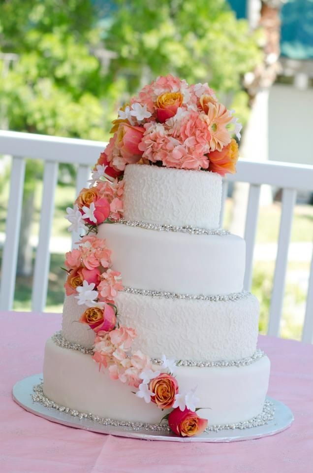 White paisley wedding cake with coral flowers and silver pearls
