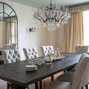 Love the mirror. Tufted chairs pair well with the dining table. Chandelier feels too stuffy though.