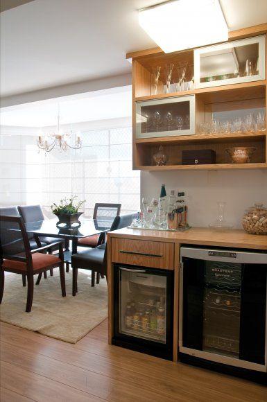 Um bar-cristaleira foi desenhado pelas arquitetas em MDF com lâmina carvalho e portas de correr com perfil metálico e vidro transparente. O móvel conta com frigobar e adega climatizada.
