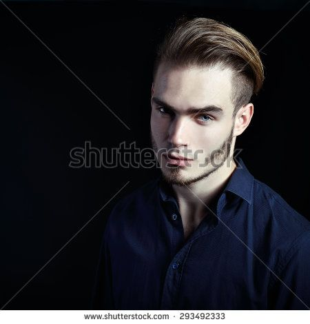 Portrait of beautiful charming young man with blue eyes and fair hair over black background, toned