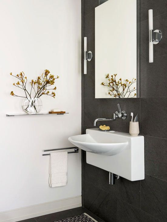 Wall-Mounted Bathroom Sink:Large slate tiles provide the backdrop for this shapely wall-mount sink, and rectangular mirrors reinforce the sleek, modern look. Wall-mount sinks can be placed to accommodate people of any height.