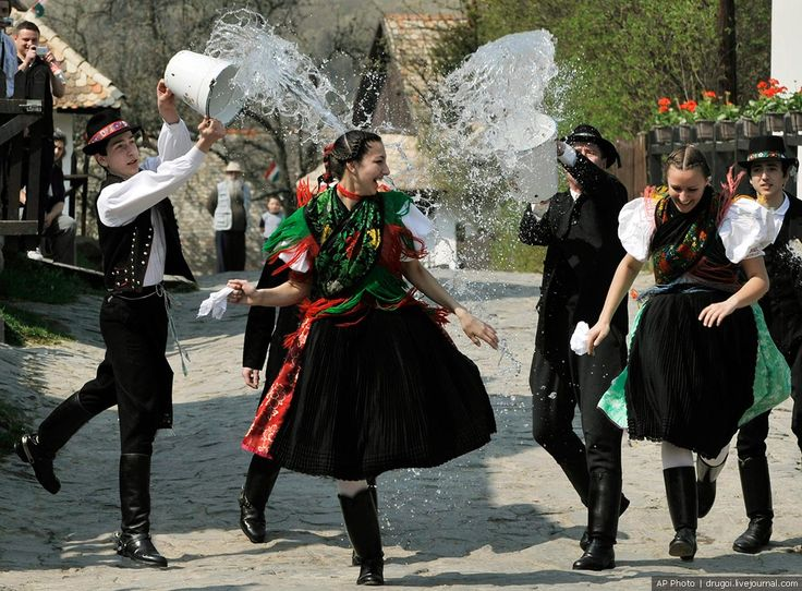 Boys of the Paloc minority, dressed in traditional clothing, pour buckets of water on girls during the rehearsal of a traditional Hungarian Easter tradition, in Holloko