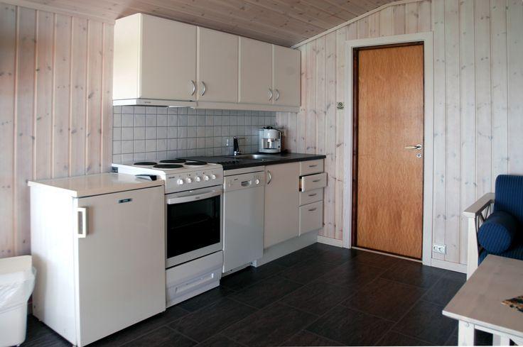 Kjøkkenbenk med tilhørende utstyr, komfyr, kjøleskap, oppvaskmaskin og mikrobølgeovn.