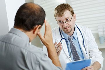 a doctor consults with his patient about health symptoms