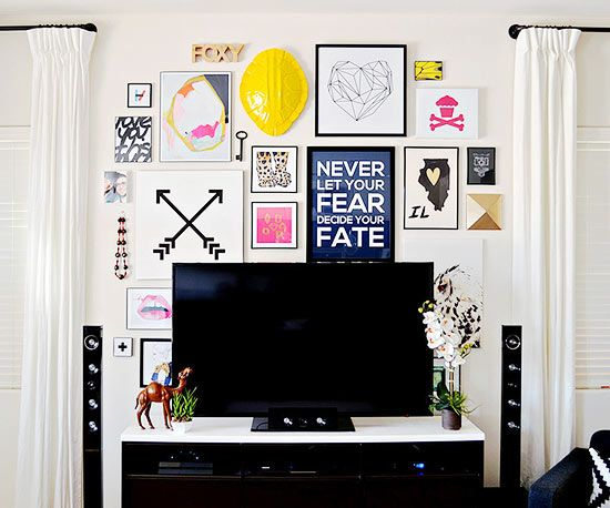 Today's updated gallery walls are an excellent way to distract from less-than-ideal must-haves in a space -- like a television. Just don't go overboard with the overall design of the space. Keep the rest of the room based in neutrals, as seen here with the simple white drapes and neutral wall color -- they help to balance the bold artwork. /