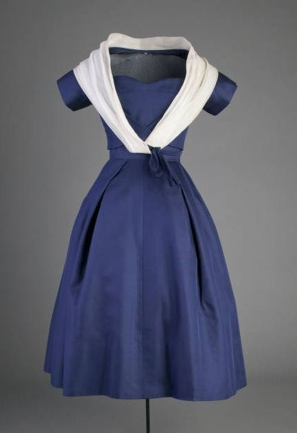 """Cocktail Ensemble, Christian Dior, Paris, France: 1956, silk taffeta, silk organza. """"Of the spring 1956 collection- the Tulip line- Vogue reported, """"Not since 1947 and Dior's famous first Collection have Paris fashions had such a rush of femininity- nor have there been so many bravos at the dramatic end of an opening."""" The small jacket cut high to reveal the waist of the skirt, called a """"Caraco"""" was a common element of the Tulip line."""""""