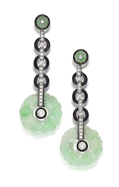 A pair of art deco onyx, jadeite jade and diamond pendant earrings, circa 1925  each designed as a carved jadeite jade bi suspended from a line of old European-cut diamonds and circular onyx links and completed by a jadeite jade and diamond surmount of floral motif; mounted in platinum; length: 2 7/8in.