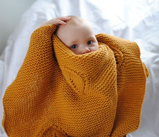Doesn't this little one look cozy! This simple baby blanket is knit in DROPS Nepal, but you can use any worsted weight yarn! Find your colors at www.nordicmart.com