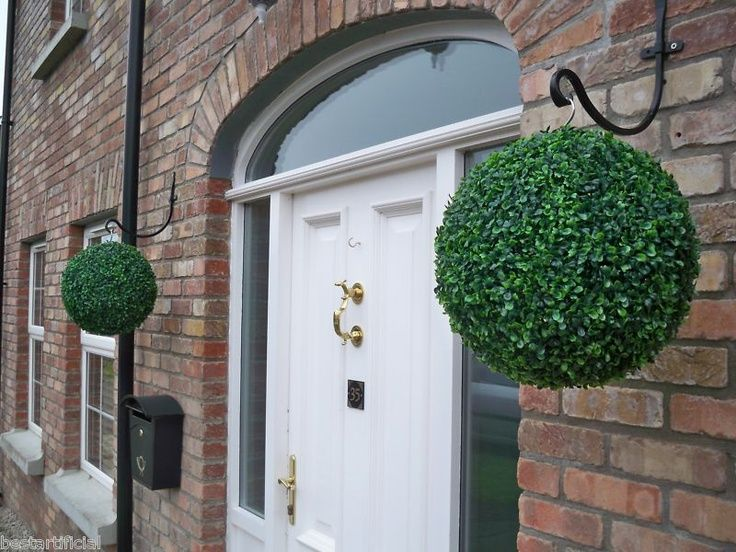 Love this front door and faux boxwood balls hanging from plant hanger hooks - very classy!