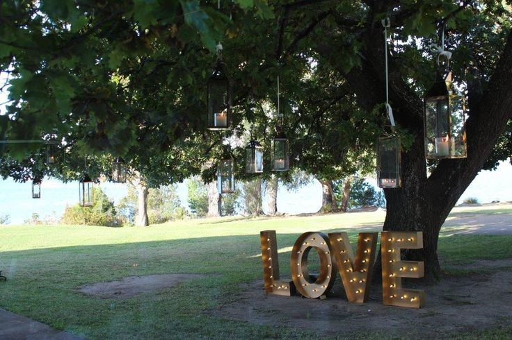 Peppermint Bay wedding with copper lanterns and LOVE sign under the tree for guests to enjoy from the reception room