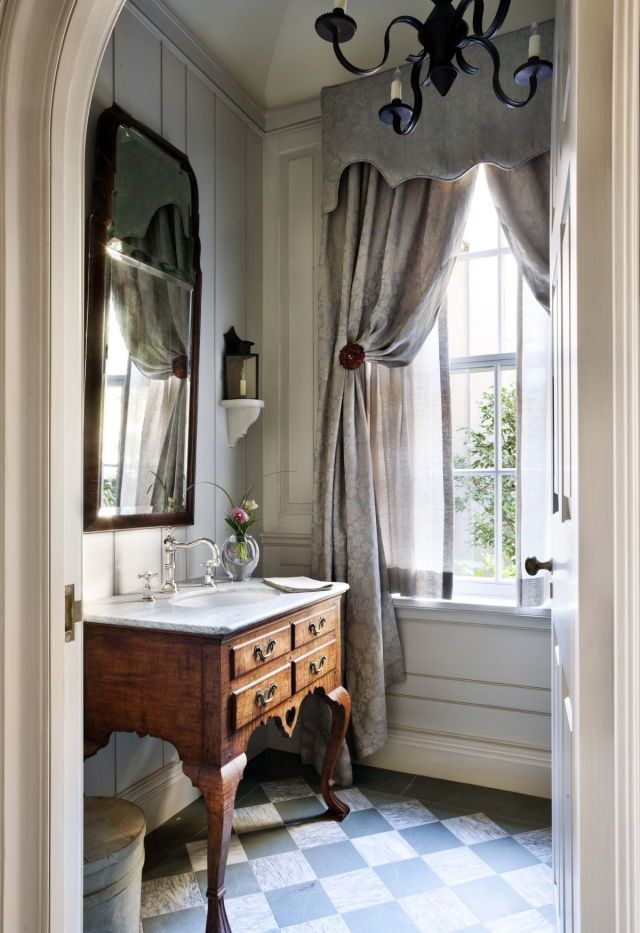 Gray bathroom, muted gray checkerboard floor in an 8 inch size maybe? (my fave in here, I could even see it in a skate blue and gray), subtle paneled wood walls, antique console used as sink cabinet, formal gray linen drapes (I could do without the too large, limp cornice).  This bathroom has a lot of lovely things going for it. Design credit? Photo credit?
