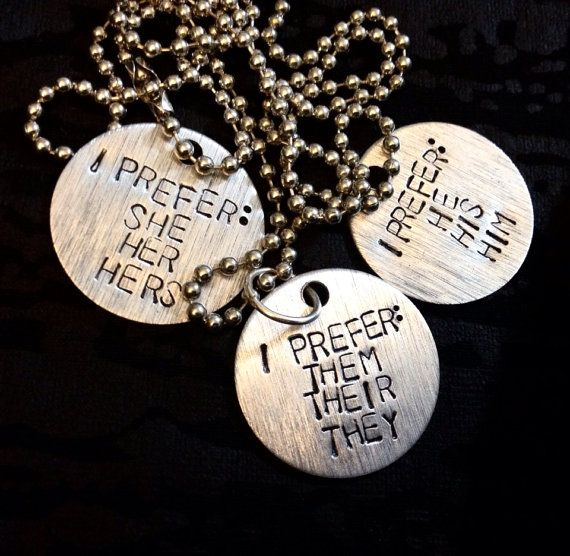 Etsy seller The Paper Poppy Store makes metal pendants and keychains hand-stamped with your pronouns. These can suit you if you also wear dog tags or want a rugged look. Available as a necklace pendant or a keychain. Available pronouns: any, custom. Ships worldwide from USA. USD$24.