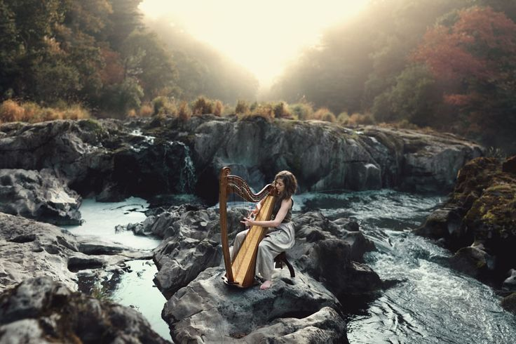 Girl playing harp in the morning mist at Cenarth falls, West Wales