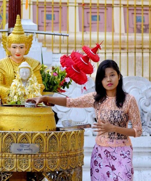 Beautiful Burmese girl pouring water on her planet at Shwedagon pagoda in Yangon.