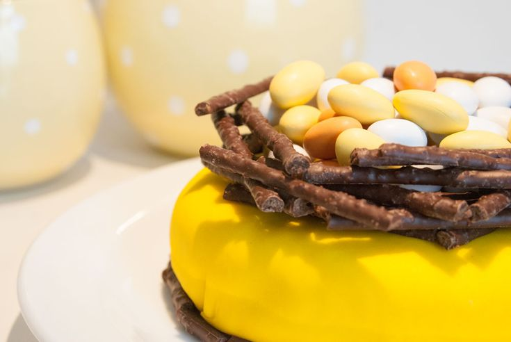 Easter cake made with yellow fondant, chocolate eggs and chocolate Sticks. Easy to make. See more at www.evabyeva.dk