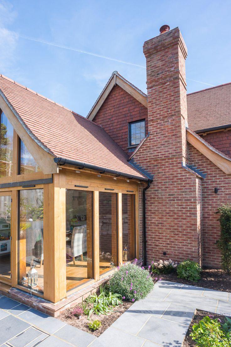 New Build Family Home, Storrington %Side view of sunken Glulam timber framed garden room, set around Indian slab stone terrace and mature planting.?u