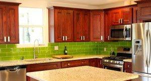 This is a great modern kitchen with cherry cabinets and lime green glass tile backsplash. Very colorful!